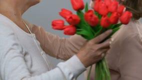 Vuxen dotter som ger blommor till den höga mamman, respekt för äldre utveckling arkivfilmer