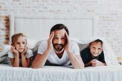 Vuxen förälder och två ungar som lägger på säng fotografering för bildbyråer