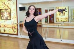 Vuxen flicka i svart klänning i dansgruppen royaltyfri bild