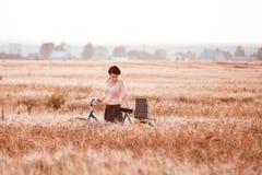 Vuxen flicka på en cykel i ett fält av råg med gåvor med ett tomt utrymme under texten arkivbild