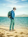 Vuxen fotvandrare med ryggsäcken på kusten av sjön arkivfoton