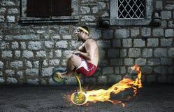 Vuxen galen man som cyklar på barns cykel Arkivfoton