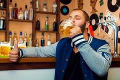 Vuxen grabb i en stång som dricker ett läckert exponeringsglas av ljust öl Arkivbilder