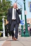 Vuxen hög affärsman som ler att gå royaltyfri foto