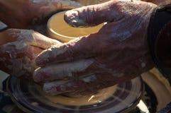 vuxen hand som matas baby& x27; s-händer som arbetar med en potter& x27; s-hjul Royaltyfri Fotografi