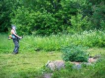Vuxen kvinna i en skyddande maskering som rymmer en banderoll och mejar gräs Fotografering för Bildbyråer