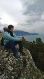 Vuxen kvinna i jeans och ett omslag under en vandring i bergen Sitta på en vagga och se den sceniska sikten Arkivbilder