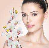 Vuxen kvinna med den härliga framsidan och blommor Arkivfoto