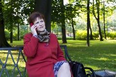 Vuxen kvinna med en trött framsida som talar på telefonen royaltyfri fotografi