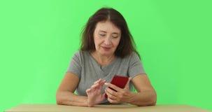 Vuxen kvinna som använder telefonen på chromakey stock video