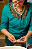 Vuxen kvinna som bryter det rå ägget i en bunke, på det inhemska köket royaltyfria bilder