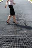 Vuxen kvinna som försöker att balance på höga hälskor royaltyfria foton