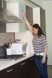 Vuxen kvinna som gör ren möblemanget Arkivfoton