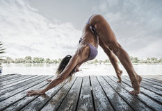 Vuxen kvinna som gör yoga i bikini på träflodflotten Arkivfoto