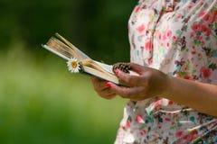 Vuxen kvinna som läser boken på grön äng Arkivfoton