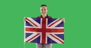 Vuxen kvinna som rymmer den engelska flaggan på den nyckel- gröna skärmen för chroma stock video