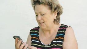 Vuxen kvinna som talar med maken som använder den smarta telefonen stock video
