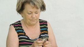 Vuxen kvinna som utomhus rymmer en smart telefon arkivfilmer