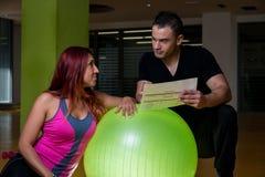 Vuxen kvinnlig med den personliga instruktören på idrottshallen Arkivbild