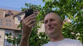 Vuxen le man som vinkar på den videopd appellen med smartphonen Video appell som talar via internet, video som pratar på den smar arkivfilmer