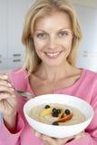 vuxen människa som äter den mitt- porridgekvinnan för ny frukt royaltyfria foton