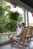 Vuxen man för sammanträde på terrassen med USA flaggor Arkivfoto