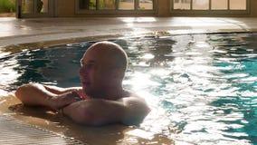 Vuxen man för stående som kopplar av i near kant för simbassäng i lyxigt hotell arkivfilmer