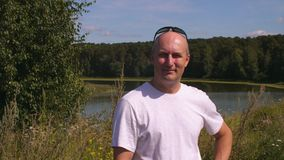 Vuxen man för stående som ler och ser in i kamera i sommarskog med sjön lager videofilmer