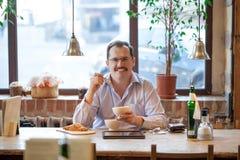 Vuxen man i kafé Fotografering för Bildbyråer