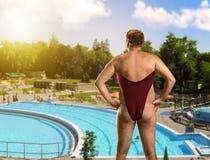 Vuxen man i kvinnas baddräkt Arkivfoto
