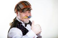 Vuxen man med en mustasch i ett lock och en waistcoat med en fjäril Det ?r en materia av f?rtroende arkivfoto
