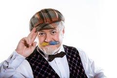 Vuxen man med en mustasch i ett lock och en waistcoat med en fj?ril Det ?r en materia av f?rtroende royaltyfria foton