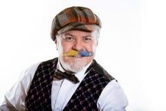 Vuxen man med en mustasch i ett lock och en waistcoat med en fj?ril Det ?r en materia av f?rtroende fotografering för bildbyråer