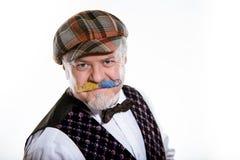 Vuxen man med en mustasch i ett lock och en waistcoat med en fj?ril i studion royaltyfri bild