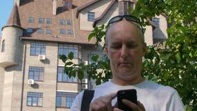 Vuxen man med solglasögon på huvudet som pratar på mobiltelefonen lager videofilmer