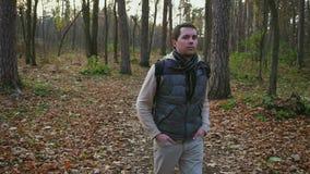 Vuxen man med svart hår med ryggsäcken som promenerar i höstskogen lager videofilmer