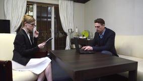 Vuxen man och kvinna i affärsklänningen som sitter i ljust rum och arbeta arkivfilmer