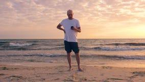 Vuxen man som använder telefonen på den härliga kusten i morgonen lager videofilmer