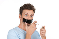 Vuxen man som försöker att avsluta röka på vit bakgrund Fotografering för Bildbyråer