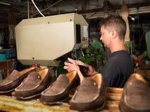 Vuxen man som fungerar i en skofabrik arkivbilder
