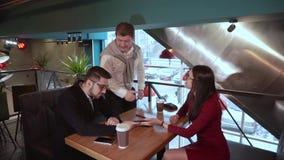 Vuxen man som kramar en grabb och ett flickasammanträde i ett kafé efter en vänlig konversation stock video
