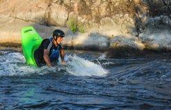 Vuxen man som paddlar en kajak på floden royaltyfria bilder