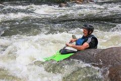 Vuxen man som paddlar en kajak på floden arkivfoton