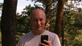 Vuxen man som talar vid videoen cal i mobiltelefon medan lopp i sommarskog stock video