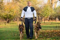 Vuxen man som utomhus går med hans tyska herde för hundkapplöpning Royaltyfri Bild