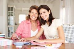 Vuxen moder och dotter som scrapbooking Arkivfoton