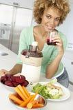 vuxen ny fruktsaft som gör den mitt- grönsakkvinnan Arkivbild