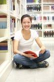 Vuxen studentläsning i libray Arkivfoton