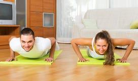 Vuxet folk som inomhus gör yoga Arkivfoto