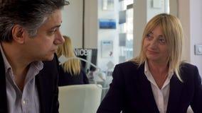 Vuxet gift par som ser de och att diskutera lån i banken som krediterar royaltyfri bild